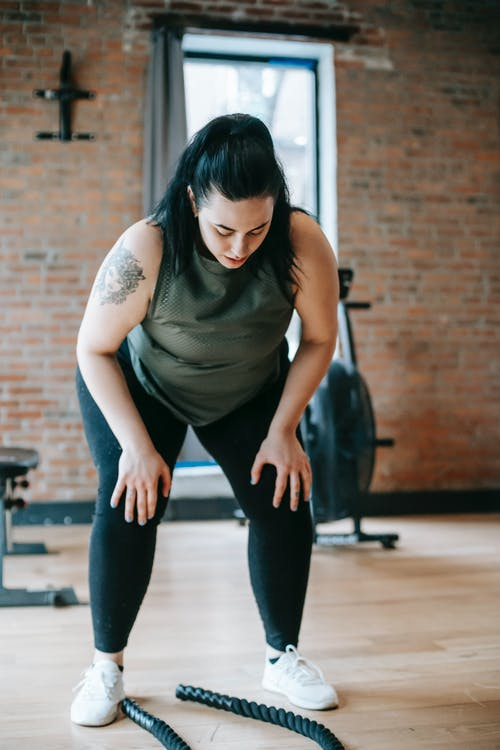 Tired woman leaning on knees during training with battle ropes