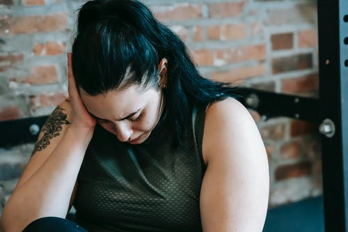 Upset female sitting near sports equipment and feeling desperate and hopeless at training in fitness club