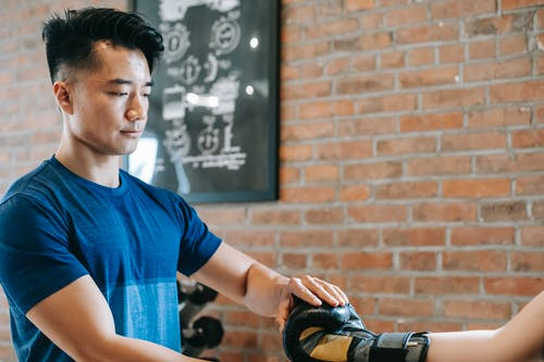 Serious Asian trainer putting on woman gloves before workout