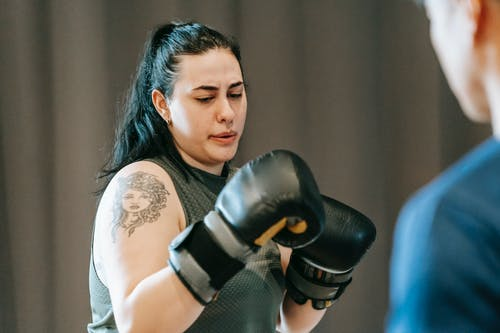 Female practicing boxing skills with trainer