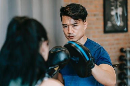 Woman in boxing gloves punching paw of concentrated Asian personal instructor during workout in gym