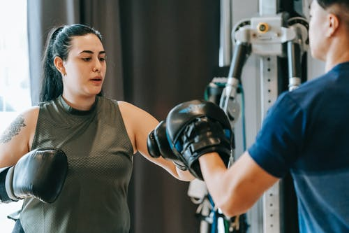 Determined female hitting personal trainer in gym