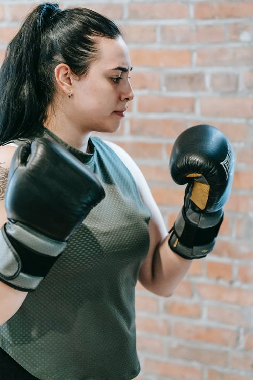 Side view of enduring woman wearing sportswear and boxing gloves standing in gym during workout