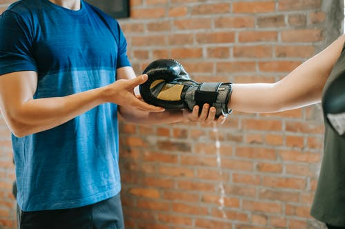 Personal trainer helping woman putting on gloves