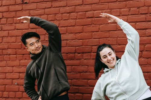 Positive young obese woman and Asian male trainer in sportswear warming up before outdoor training standing near brick wall
