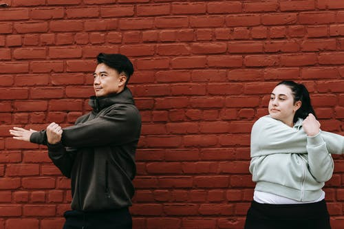 Active young plus size female and Asian male trainer in activewear warming up arms near brick wall during outdoor workout in city