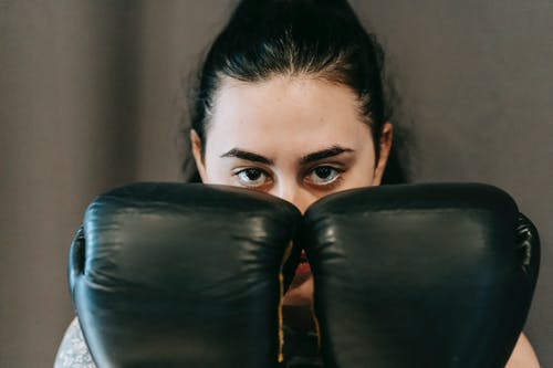 Concentrated young female athlete with long dark hair covering face with hands in boxing gloves during training