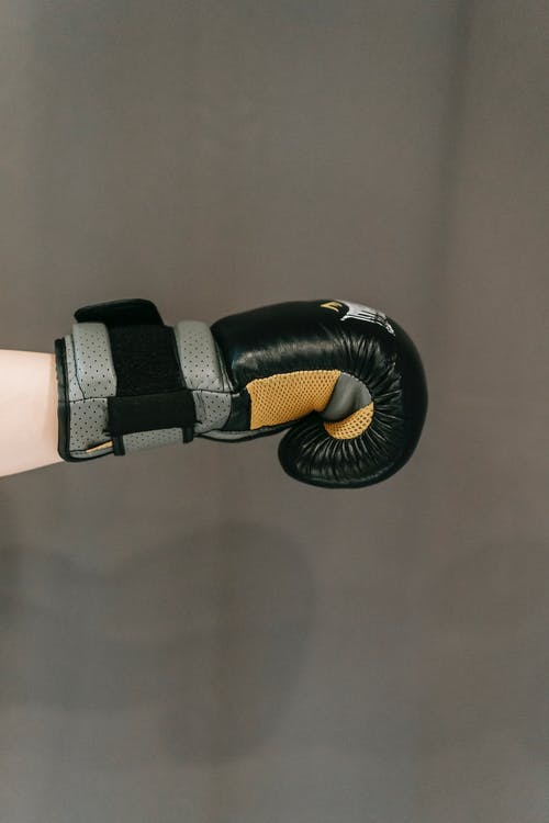 Side view of crop anonymous person in boxing gloves punching against gray background during workout
