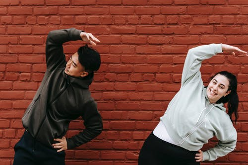 Positive young plus size female and fit Asian male trainer standing near brick wall and doing Overhead Side Reach Stretch exercise before workout on street