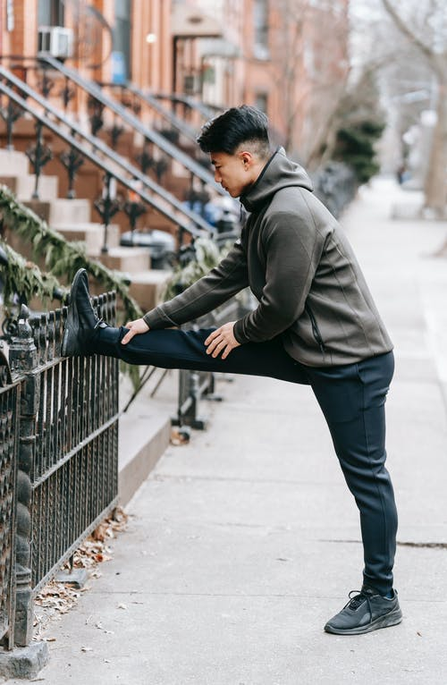Sporty young ethnic guy stretching leg on street after jogging