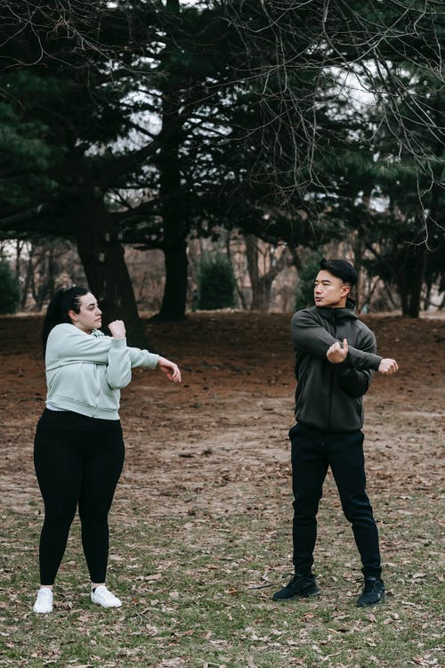 Full body of Asian man and plus size woman doing exercises in autumn park with dry leaves