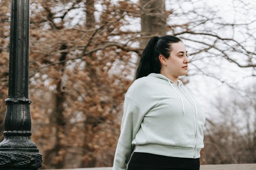 Overweight woman standing in autumn park and looking away