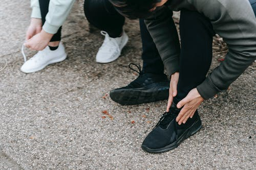 Crop unrecognizable people in warm sportswear tying shoelaces of sneakers on street in daytime