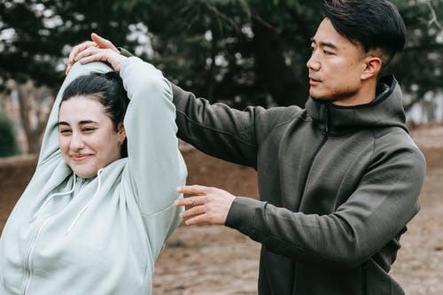 Positive overweigh woman stretching arms with Asian trainer in park