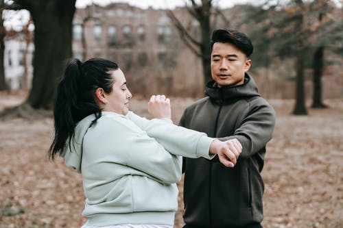 Serious Asian trainer in outerwear holding hands of focused female during training in autumn park in daylight