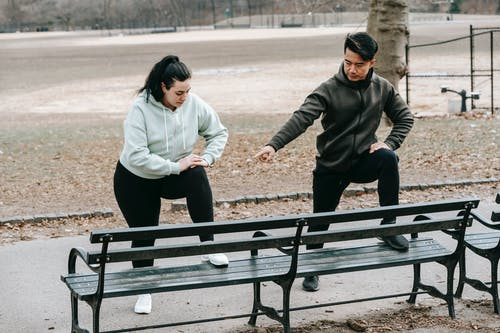 Asian trainer teaching woman doing sports exercise in park