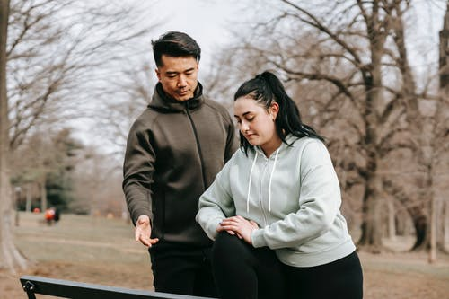 Multiethnic couple in sportswear training in park on bench