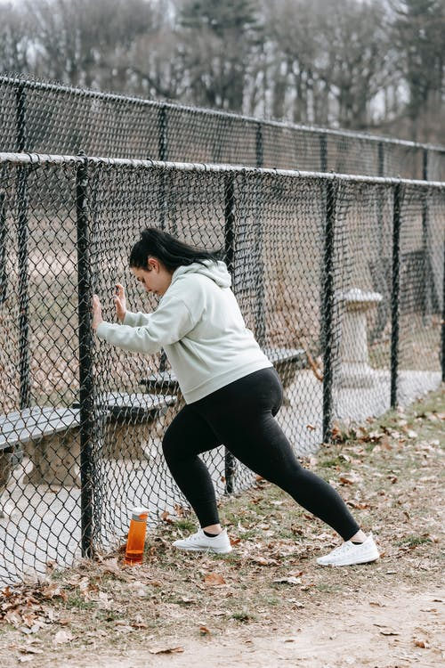 Side view of determined plus size female athlete in sportswear leaning on chain link fence while training in city park on cloudy autumn day