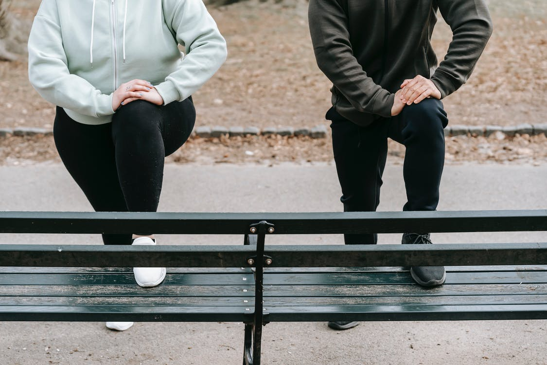Crop faceless fit man and overweight woman putting legs on wooden bench while training together in autumn park