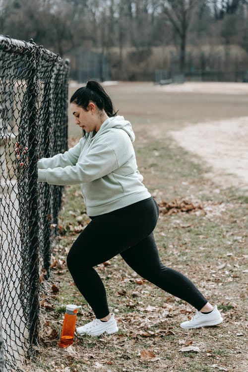 Determined young woman exercising in autumn park leaning on chain link fence