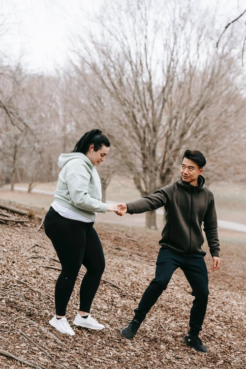 Full body of positive ethnic trainer giving hand to oversize woman in autumn park with dry leaves