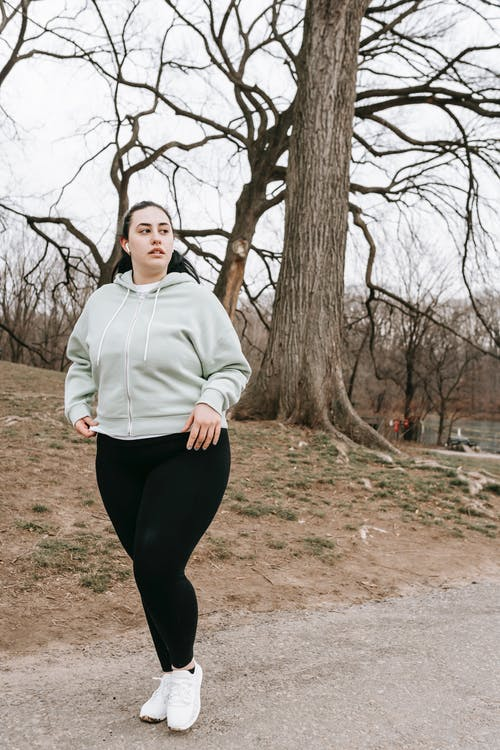 Plus size young woman in sportswear training in park