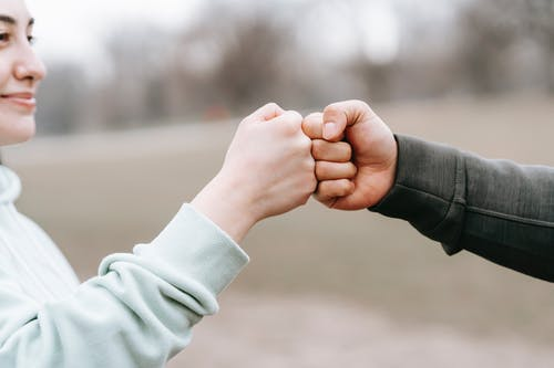 Crop anonymous cheerful woman and man giving fist bump to each other on blurred background of park