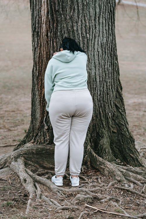 Back view of anonymous plus sized woman in sportswear standing and leaning on tree placed in forest in daytime