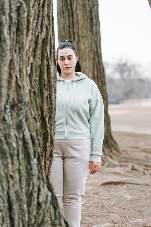 Serious overweight female standing near tree in park