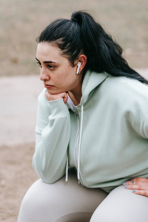 Side view of pensive overweight woman with long dark hair in sportswear and earphones sitting and looking away in park in daytime