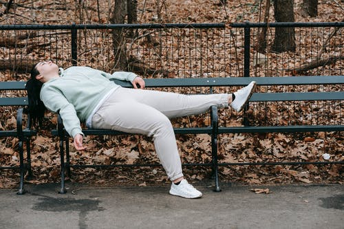 Tired overweight woman lying on bench in park