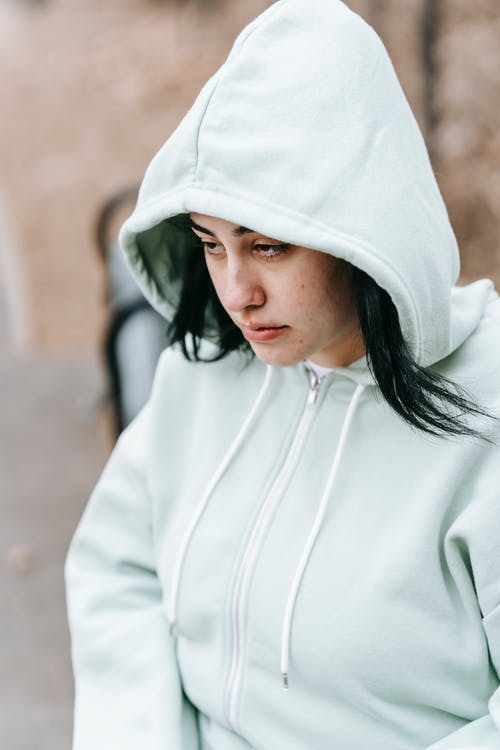 Upset young woman in hood sitting on bench