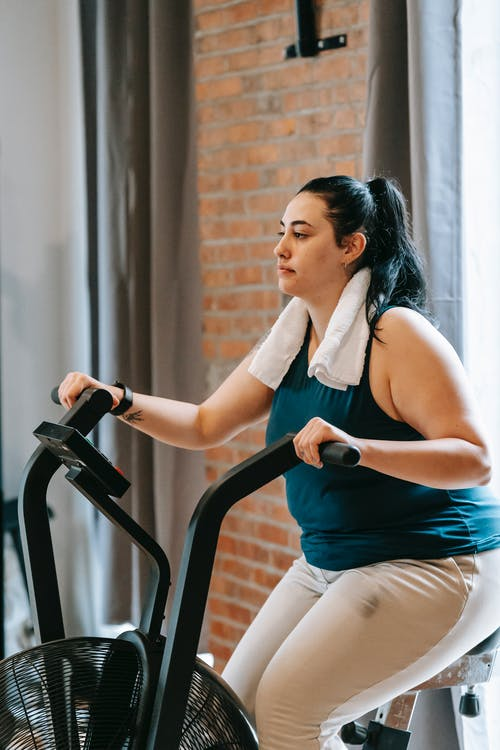 Side view of young overweight female in fitness outfit doing exercises on cycle in gym