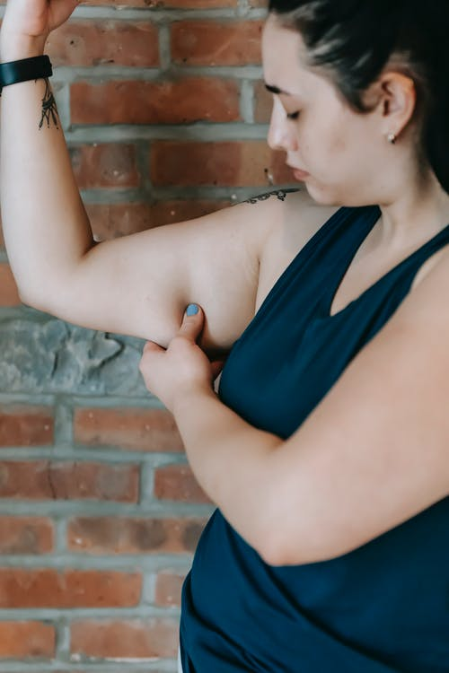 Unhappy plus size female showing excess fat on arms
