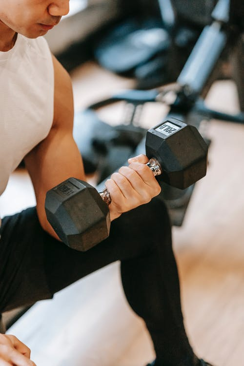 Fit man doing exercises with dumbbell