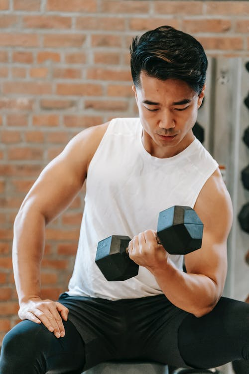 Strong Asian man lifting heavy dumbbell
