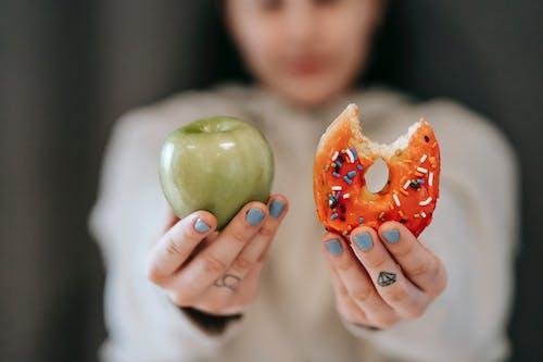 Woman showing apple and bitten doughnut