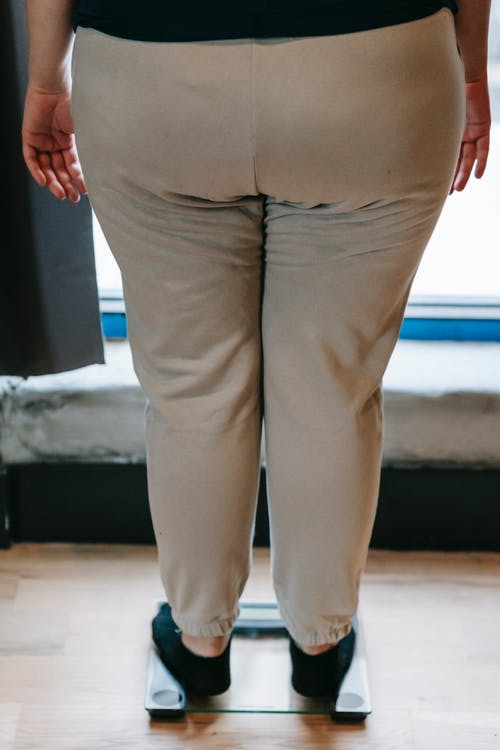 Overweight woman standing on glass scale