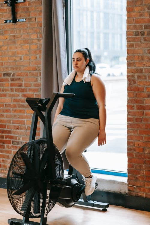 Full body of exhausted female sitting on exercise bike and putting arms down in gym after intense training