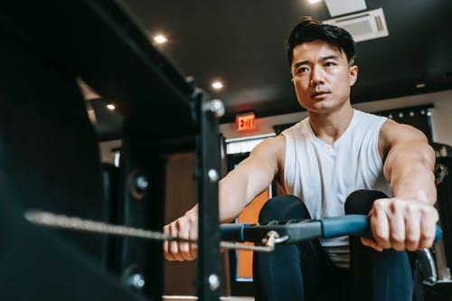 Focused ethnic sportsman doing exercises on rowing machine
