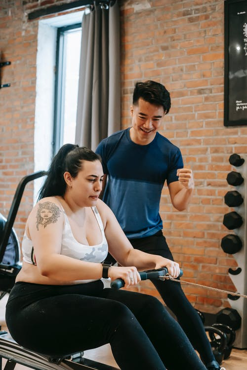 Tensed plus size woman doing exercises with trainer
