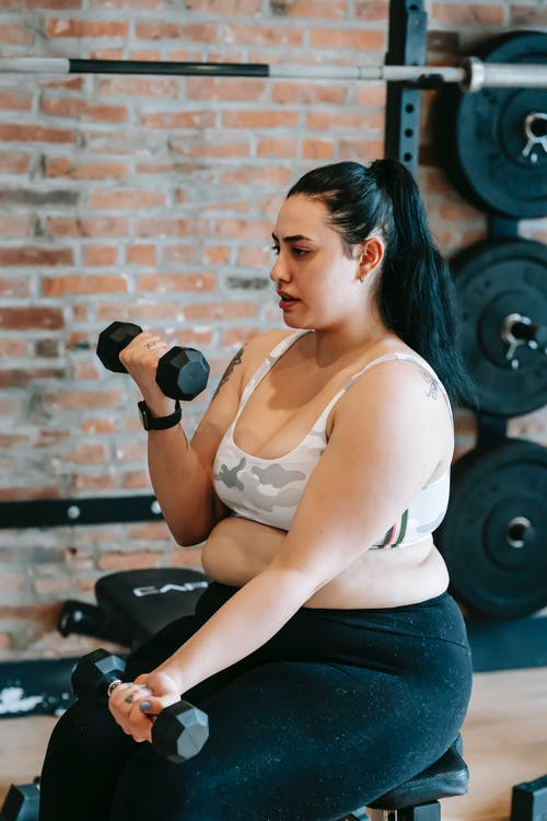 Side view of overweight female in activewear doing exercise with dumbbells during weight loss workout in sports club