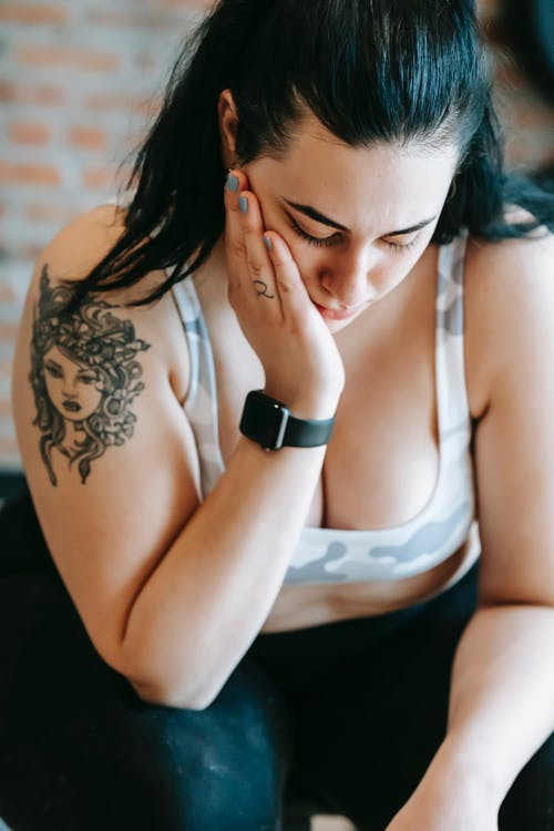 Upset overweight woman resting after training