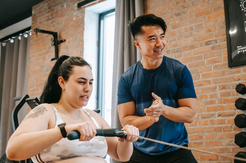 Low angle of smiling ethnic male trainer clapping hands to overweight female training on rowing machine in gym