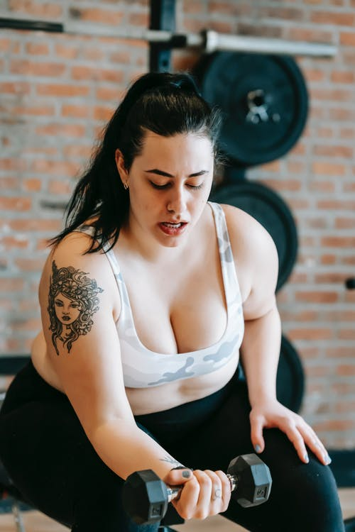 Overweight female exercising with dumbbells in gym