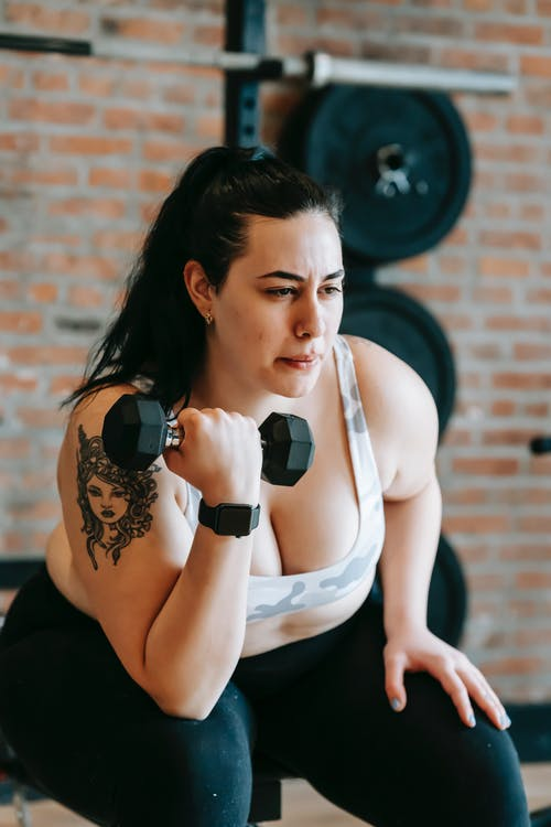 Concentrated woman in sportswear sitting on bench and lifting dumbbell during weight loss workout in gym with fitness equipment