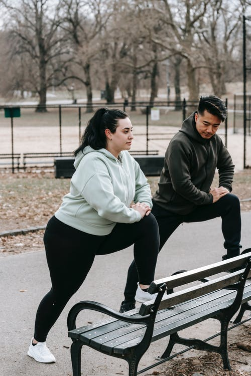 Side view of plus size woman with Asian male personal trainer in sportswear stretching legs on bench during outdoor workout in city park