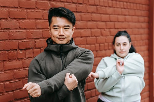 Calm Asian trainer in sportswear stretching arms while training with plus sized female against brick wall in daytime