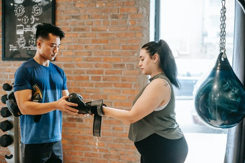 Overweight female training with trainer in boxing club