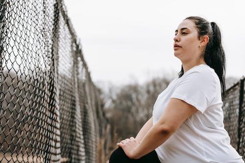 Plump woman stretching legs near net fence